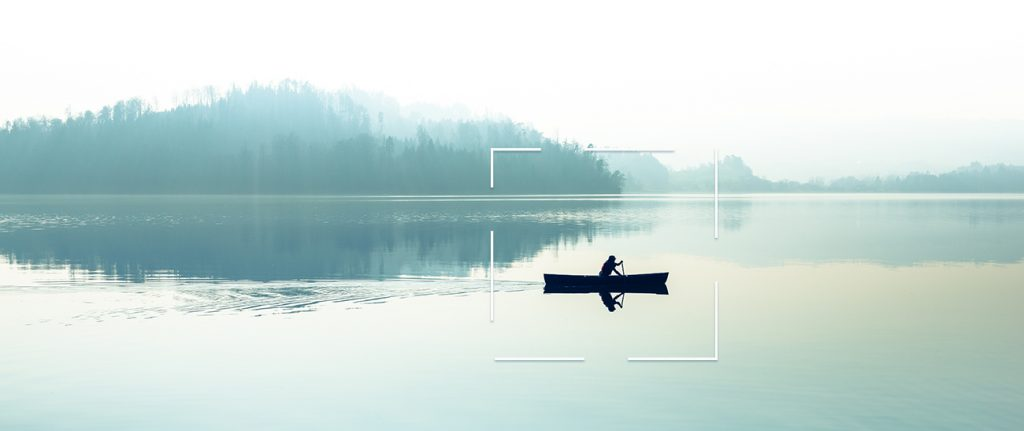 Early morning on a calm lake with a person paddling a canoe